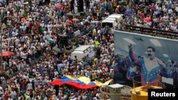 VENEZUELA – Opposition supporters take part in a rally against Venezuela's President Nicolas Maduro next to a poster of him in Caracas, Venezuela, October 26, 2016.