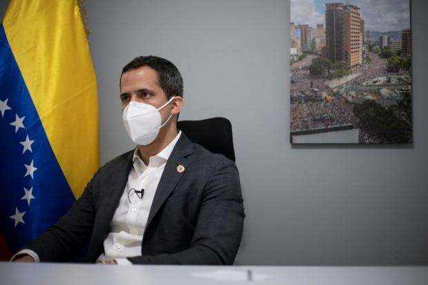 Venezuelan opposition leader Juan Guaido's home office features a national flag and a picture o...